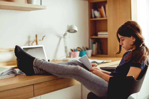 Relaxed Teenager girl doing homework stock photo