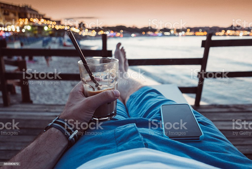 Relaxed tourist with cocktail at the beach stock photo
