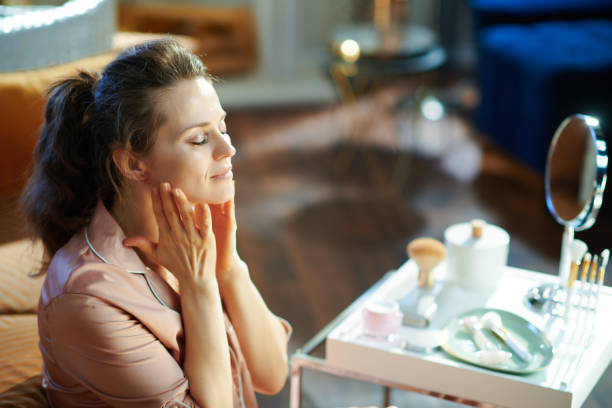 relaxed woman applying cream and making massage stock photo