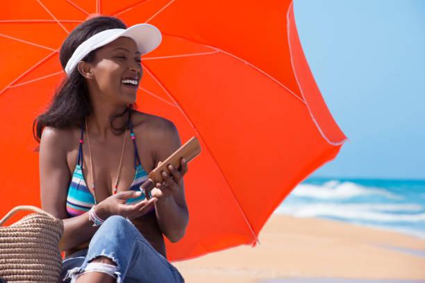 entspannte frau sonnenschutz creme auftragen, am sonnigen strand. - hautkrebs stock-fotos und bilder