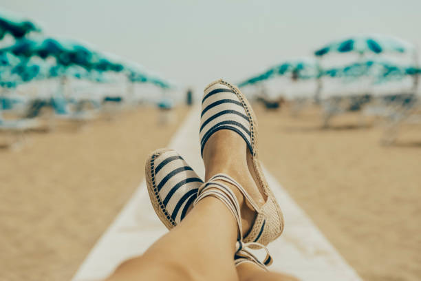 해변에서 편안한 여자 - 샌들 뉴스 사진 이미지