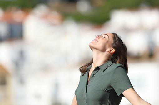 Relaxed woman breathing fresh air in a town on summer