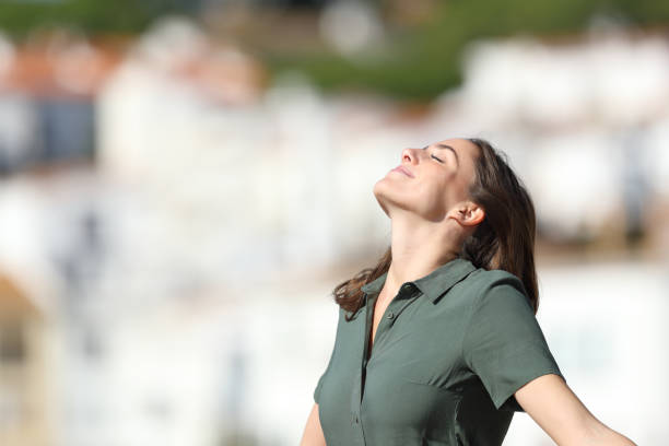 Relaxed woman breathing fresh air in a town on summer stock photo