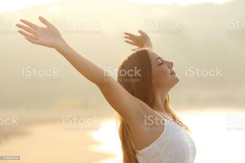 Relaxed woman breathing fresh air raising arms at sunrise foto