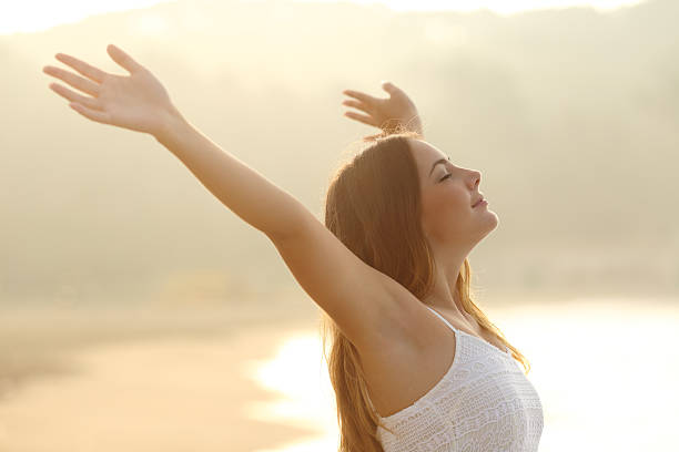 Relaxed woman breathing fresh air raising arms at sunrise stock photo