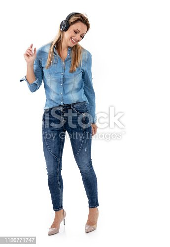 istock Relaxed woman dancing to music, using headphones 1126771747