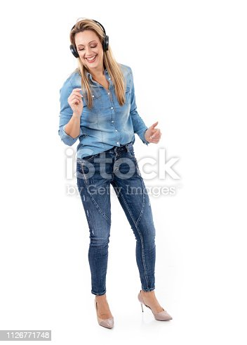 istock Relaxed woman dancing to music, using headphones 1126771748