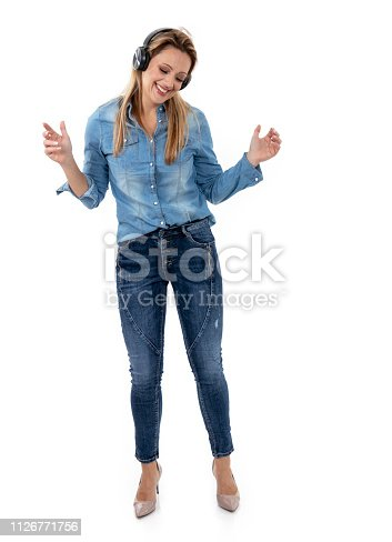 istock Relaxed woman dancing to music, using headphones 1126771756