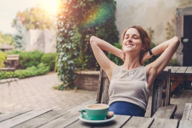 relajado mujer tomando café en el jardín - gente tranquila fotografías e imágenes de stock