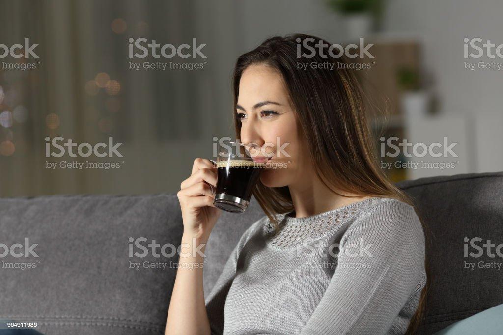 放鬆的婦女喝無咖啡因的咖啡在晚上 - 免版稅一個人圖庫照片