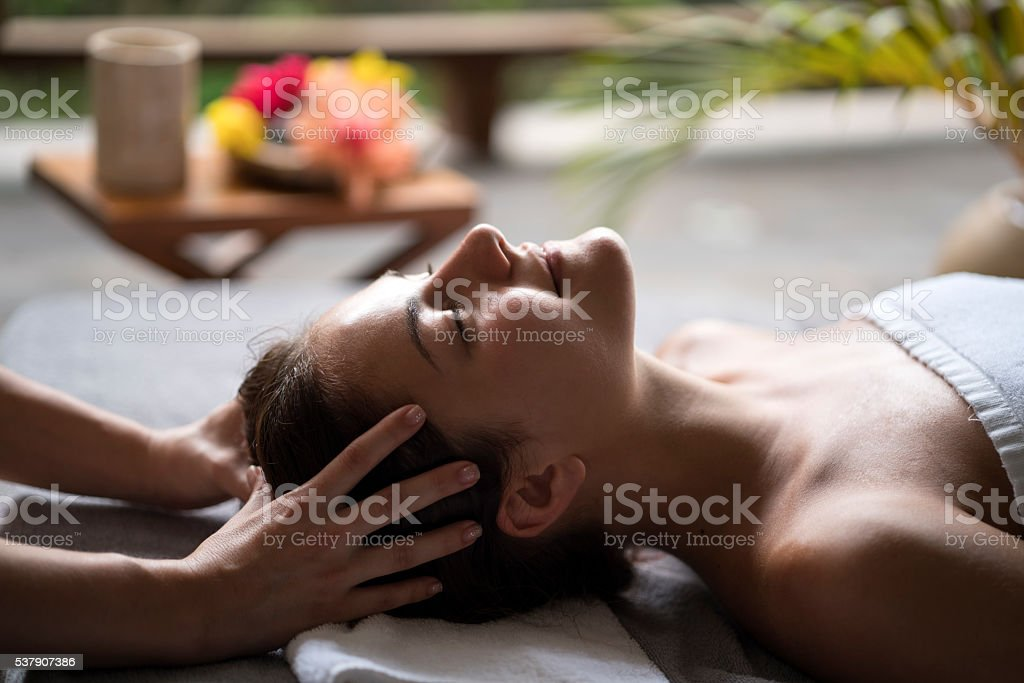 Relaxed woman enjoying in a head massage at the spa. stock photo