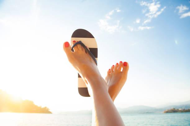 entspannte frau füße und flip flops am strand - salzwasser sandalen stock-fotos und bilder