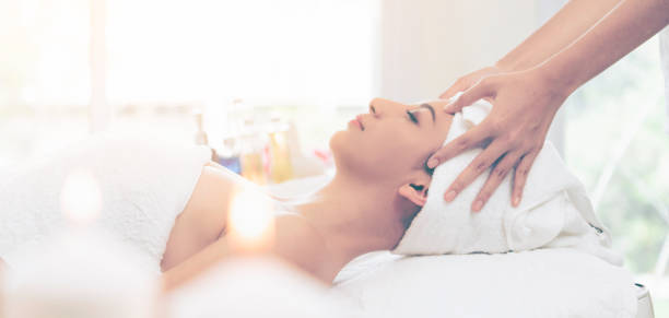 Relaxed woman gets facial and head massage in spa. stock photo