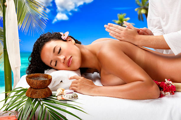 Relaxed woman getting massage therapy in Caribbean beach Spa resort stock photo
