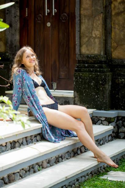 Relaxed woman in bikini sitting on stairs in yard stock photo