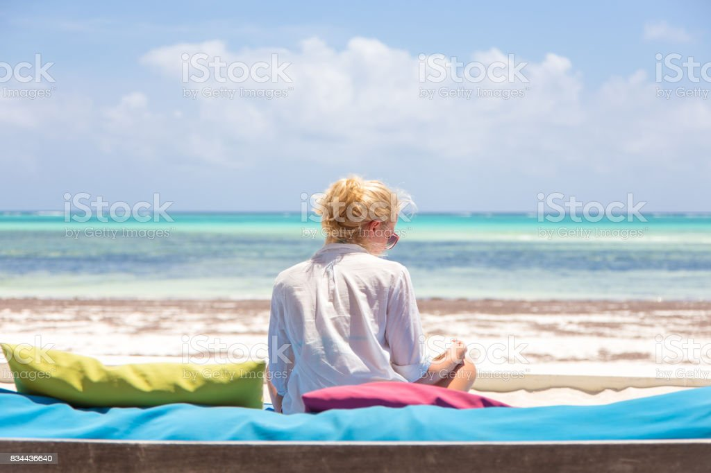Entspannte Frau im Luxus liege, Arme rised, Sommerurlaub am schönen Strand zu genießen. Lizenzfreies stock-foto