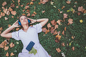Above view of woman lying down in the grass and listening to the music