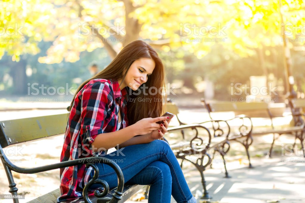 Relaxed woman in the city park texting royalty-free stock photo