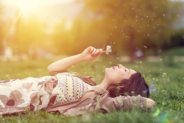 relaxed woman in the park blowing dandelion - reclining stock photos and pictures