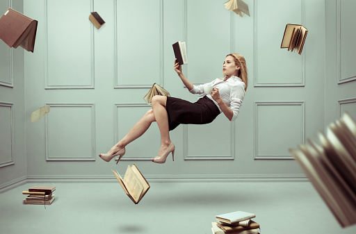 A Relaxed Woman Levitates In A Room Full Of Flying Books Stock Photo - Download Image Now