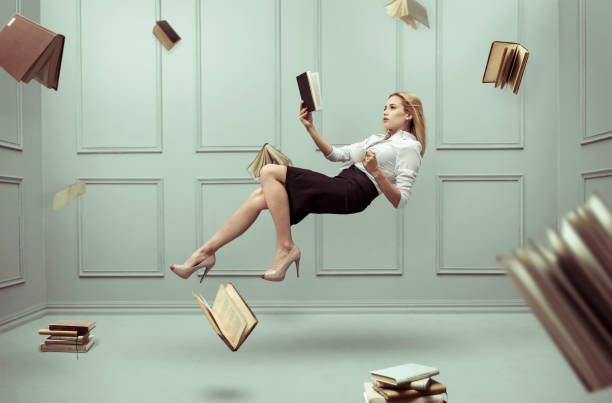 a relaxed woman levitates in a room full of flying books - volare foto e immagini stock