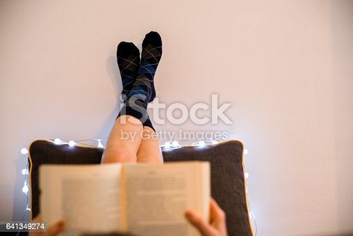 501914364istockphoto Relaxed woman lying in bed reading a book 641349274