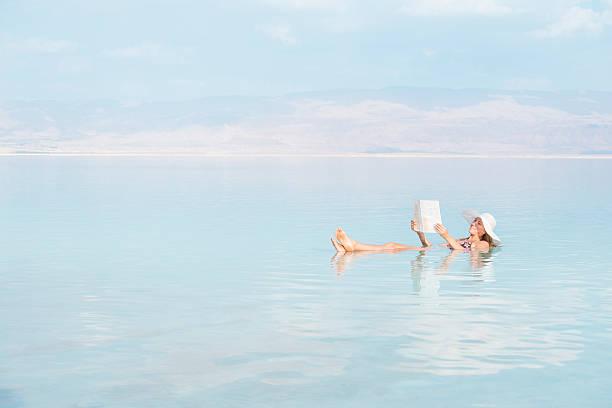 zrelaksowany kobieta czytanie gazety podczas swobodnego w morze martwe wody. - morze martwe zdjęcia i obrazy z banku zdjęć