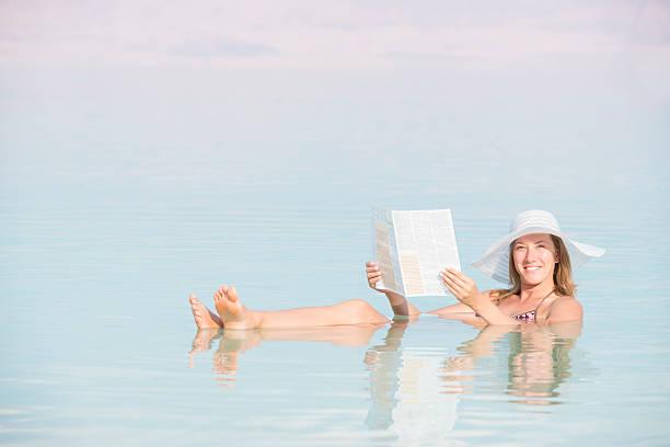 relaxed woman reading newspaper while floating in dead sea water. - newspaper beach stockfoto's en -beelden