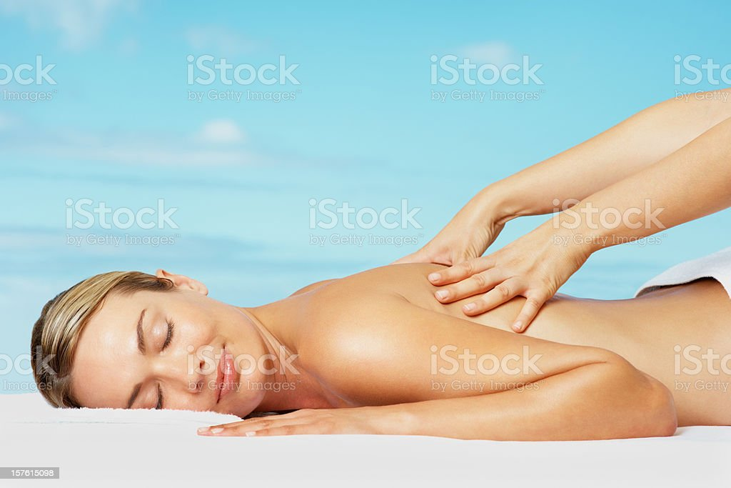 Relaxed woman receiving a back massage against blue sky royalty-free stock photo