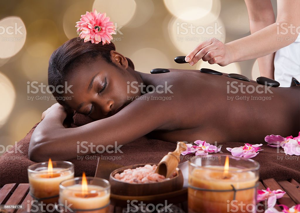 Relaxed Woman Receiving Hot Stone Therapy stock photo