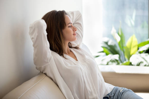 Relaxed woman resting breathing fresh air at home on sofa Relaxed calm woman resting breathing fresh air feeling mental balance enjoying wellbeing at home on sofa, satisfied young lady taking pleasure of stress free weekend morning stretching on couch relaxation stock pictures, royalty-free photos & images