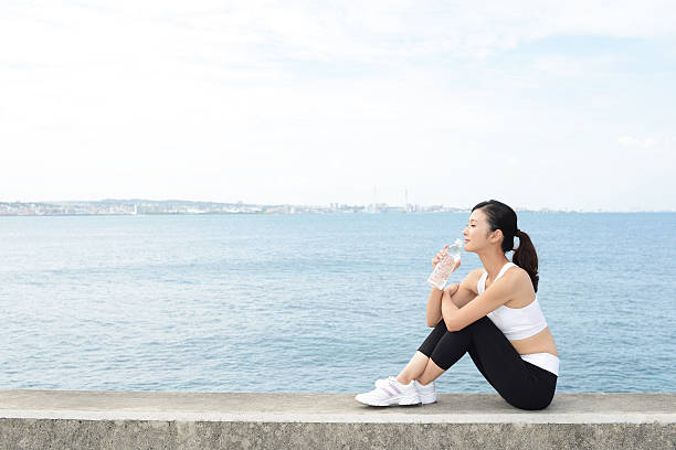 Relaxed woman sitting by the sea Smiling woman with a bottle of water groyne stock pictures, royalty-free photos & images