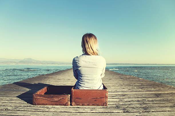 rilassata donna seduta nel suo grande valigia dopo un viaggio - donna valigia solitudine foto e immagini stock