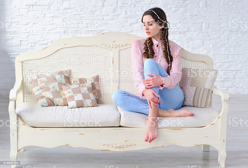 Relaxed woman sitting on a vintage sofa