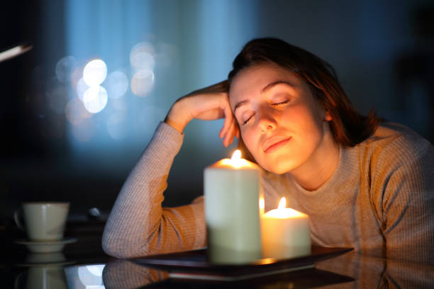 Relaxed woman smelling aromatic candles in the night stock photo