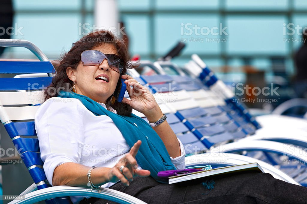 Relaxed woman talking with cellphone on cruise ship stock photo