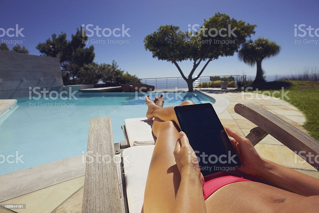 Relaxed woman using digital tablet by poolside - Royalty-free Adult Stock Photo
