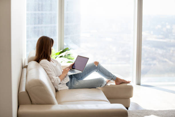 relaxed woman using laptop sitting on sofa at luxury home - choosing stock photos and pictures