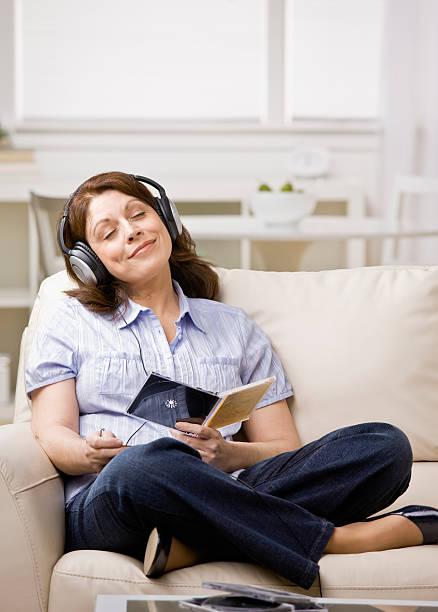 Relaxed woman wearing headphones enjoying listening to music in livingroom stock photo