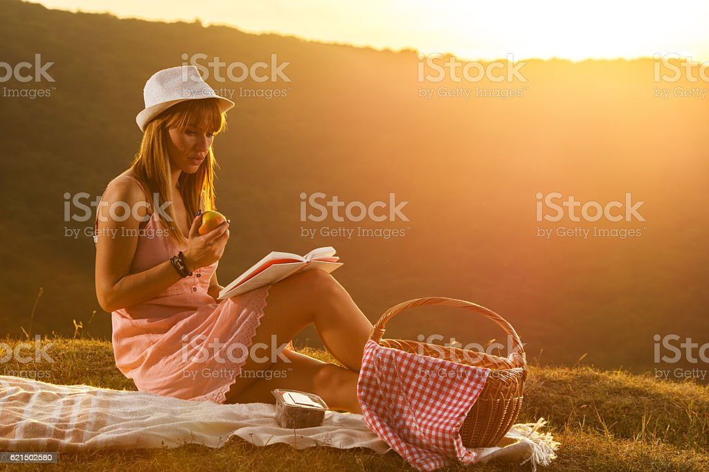 Relaxed woman with an apple reading book at picnic. photo libre de droits