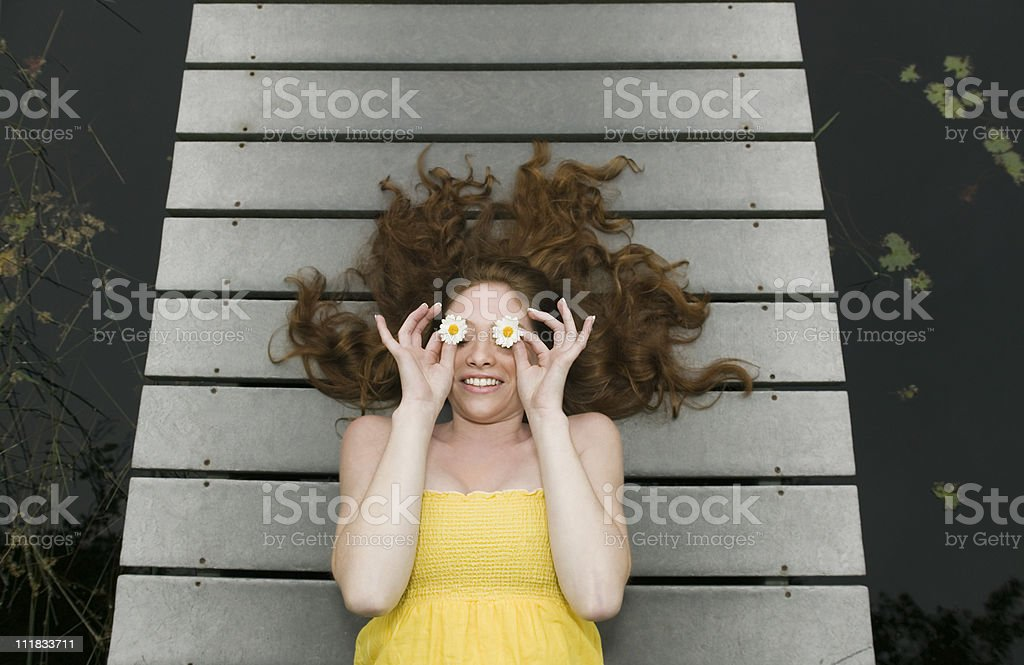 Relaxed woman with flowers over eyes stock photo