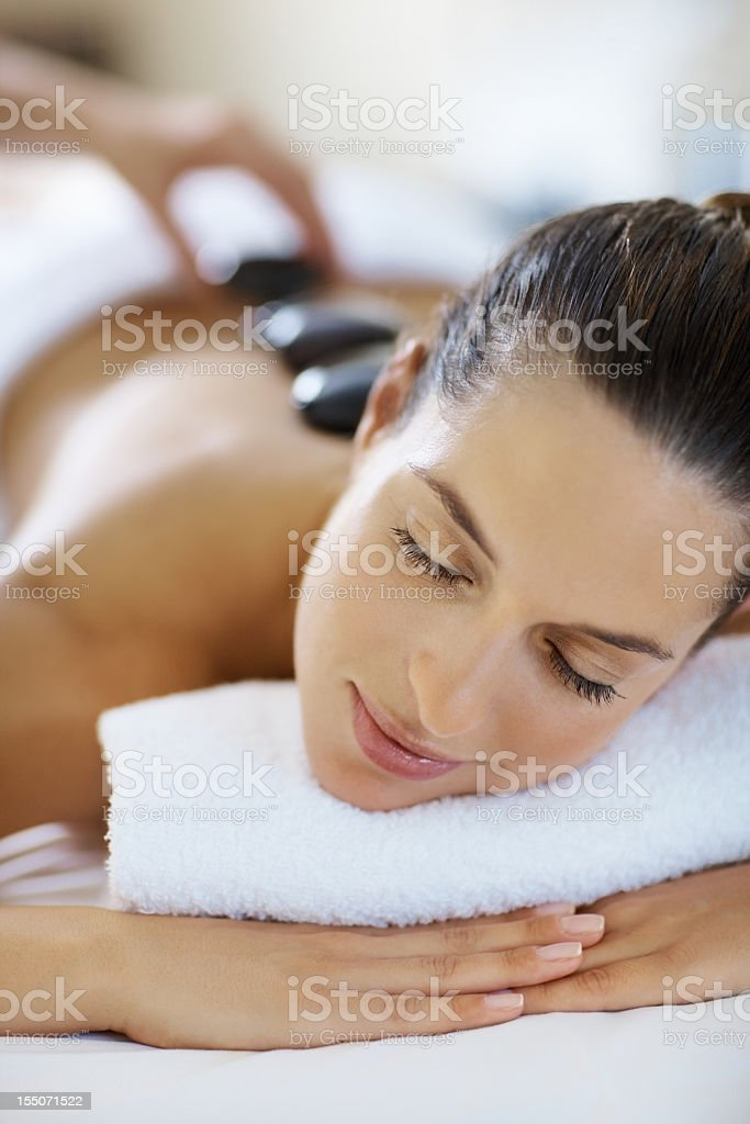 Relaxed woman with stones on back stock photo