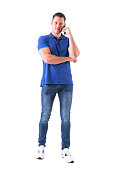 istock Relaxed young adult casual man talking on the mobile phone smiling and looking at camera 1017887914