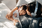 istock Relaxed young Asian mother and little daughter with eyes closed lying on the bed and listening to music with headphones 1223610900