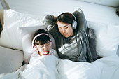 istock Relaxed young Asian mother and little daughter with eyes closed lying on the bed and listening to music with headphones 1257145571