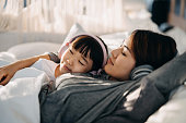 istock Relaxed young Asian mother and little daughter with eyes closed lying on the bed and listening to music with headphones 1268633595