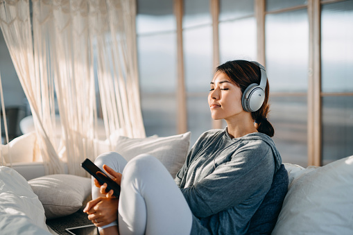 Relaxed young Asian woman with eyes closed sitting on her bed enjoying music over headphones from smartphone at home