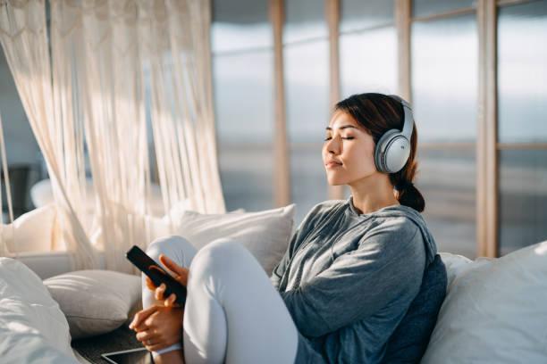 jovem asiática relaxada com os olhos fechados sentado em sua cama apreciando música sobre fones de ouvido do smartphone em casa - escapismo - fotografias e filmes do acervo