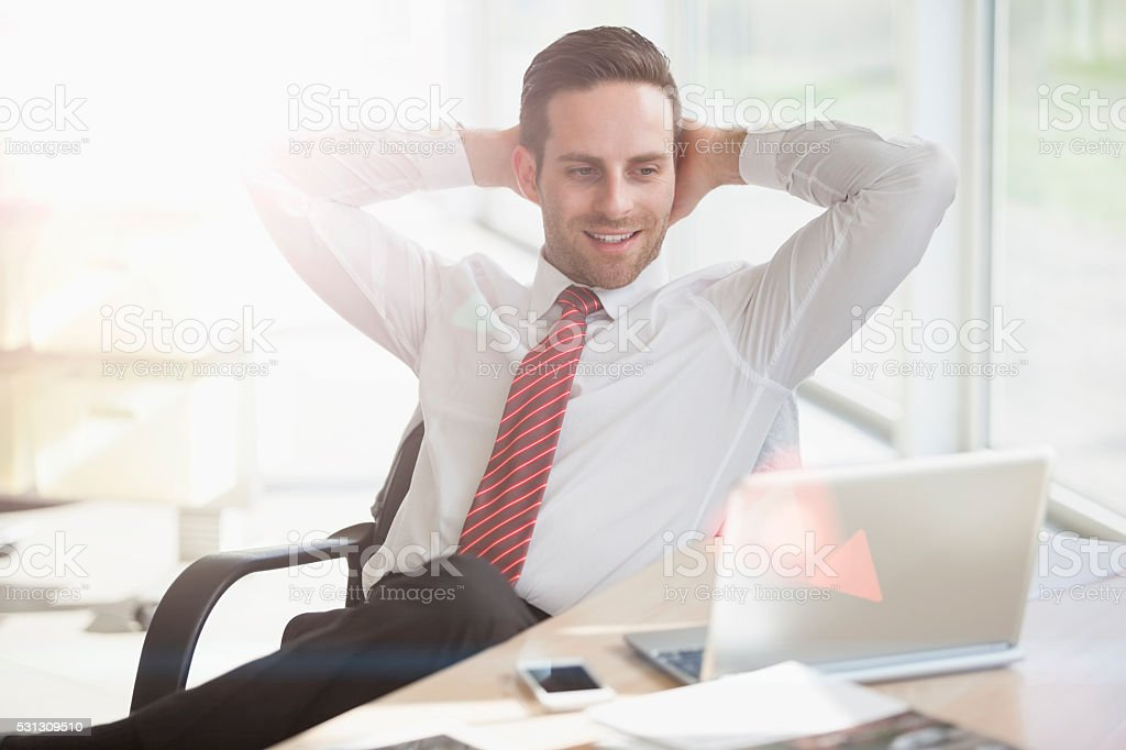 Relaxed young businessman looking at laptop in creative office stock photo