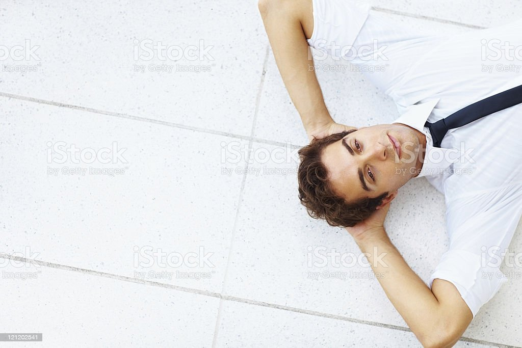 Relaxed young businessman lying on floor royalty-free stock photo